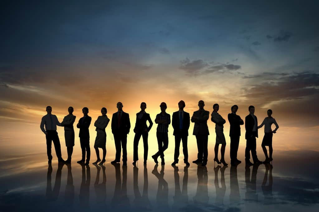 Silhouettes of group of business people standing in line on sunset background